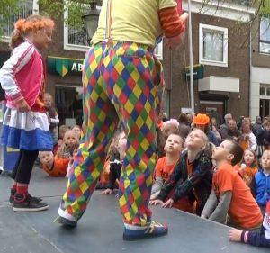 De kinderen helpen clown Kiko bij de straat-jongleer-show met goochelen