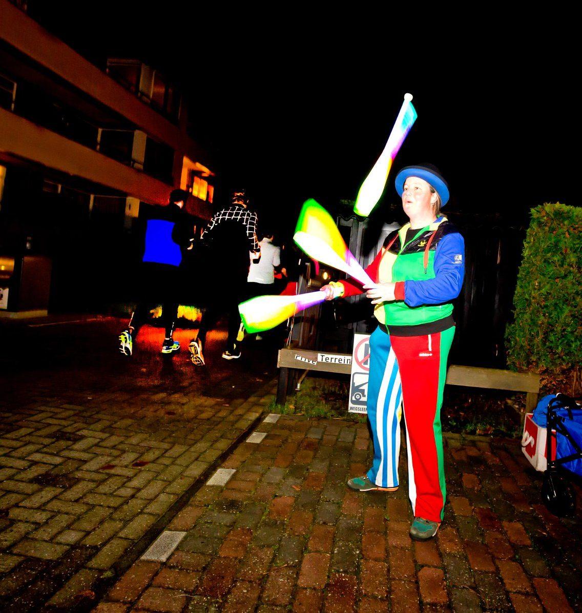 Jongleur Kiko jongleren met licht voor de voorbijkomende hardlopers van de Nedal Utrecht Nightrun